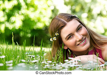 Beautiful young woman smiling outdoors with flowers