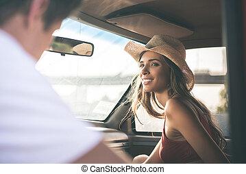 woman smiling to man in car window