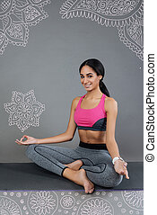 Beautiful young woman smiling while sitting on a yoga mat