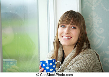 Beautiful Young Woman Smiling with Cup of Tea