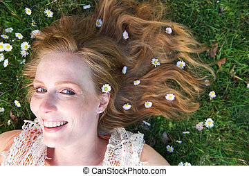 Beautiful young woman smiling with spring flowers in hair