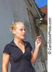 Beautiful young woman smokes a cigarette
