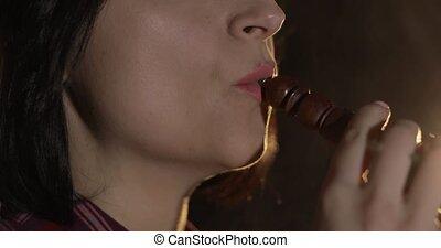 Beautiful, young woman smoking hookah. Attractive girl smoking flavored tobacco
