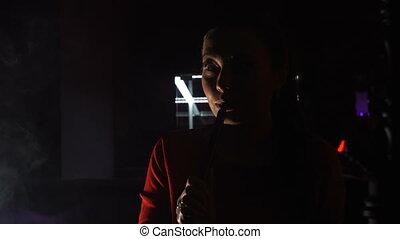 Beautiful young woman smoking hookah in dark shisha bar
