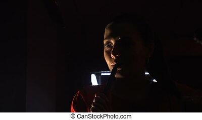 Beautiful young woman smoking hookah