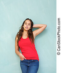 Beautiful young woman standing against blue background with hand in hair