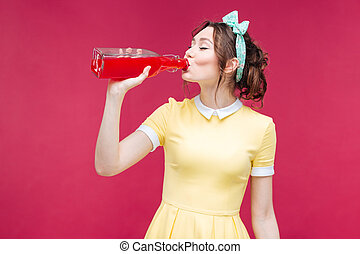 Beautiful young woman standing and drinking juice from the bottle