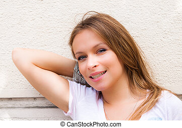 beautiful young woman standing by white wall