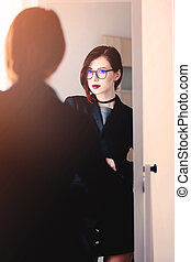beautiful young woman standing in front of mirror and looking at her reflection