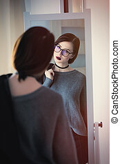 beautiful young woman standing in front of mirror, holding a jacket and looking at her reflection