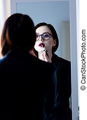 beautiful young woman standing in front of mirror, putting on lipstick and looking at her reflection