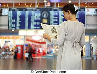 beautiful young woman standing in hall of airport and reading newspaper