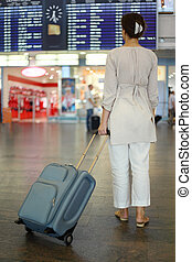 beautiful young woman standing in hall of airport with luggage and waiting airplane, focus on suitcase