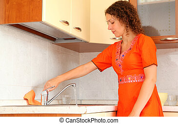 beautiful young woman standing in kitchen. She opens faucet.