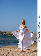 beautiful young woman standing in white dress by the sea on a Sunny day