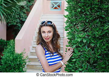 beautiful young woman standing near a green bush in a park