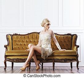 Beautiful, young woman standing near a sofa