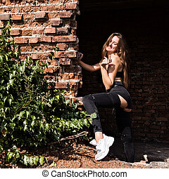 beautiful young woman standing near the brickwall in abandoned building
