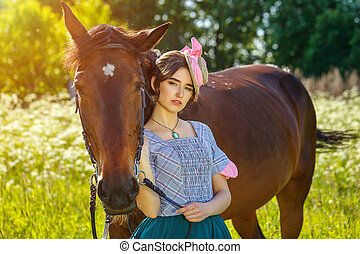 beautiful young woman standing next to a horse in nature