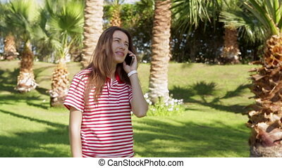 Beautiful young woman standing on a green lawn and talking on a cell phone