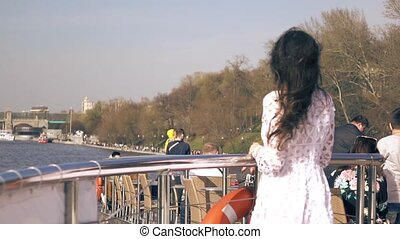 Beautiful young woman standing on the deck of a river tour boat passing famous Gorky park in Moscow. Slow motion shot