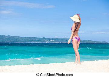 Beautiful young woman standing on the beach enjoying the sun