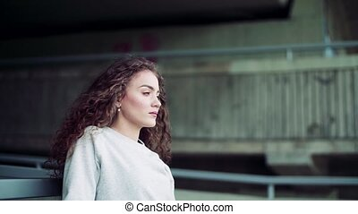 Beautiful young woman standing under the bridge in the city.