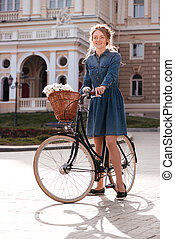 Beautiful young woman standing with bicycle in the city