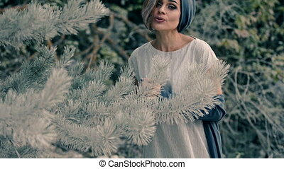 Beautiful young woman stands in the coniferous forest and sings a song