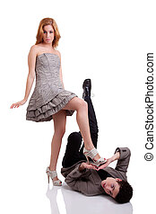 beautiful young woman stepping on a young man, isolated on ...