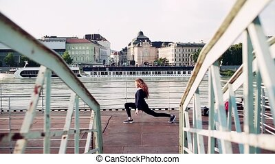 Beautiful young woman stretching by the river in the city.