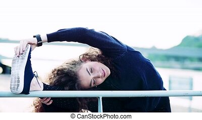 Beautiful young woman stretching legs on the railing in the...