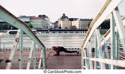 Beautiful young woman stretching on the bridge in the city.