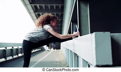 Beautiful young woman stretching under the bridge in the city.
