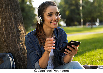 Beautiful young woman student in the park listening music with headphones using mobile phone.