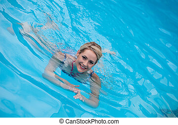 Beautiful young woman swimming in a pool
