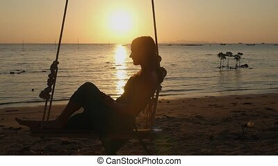Beautiful young woman swinging on a swing at amazing sunset through the sun with lens flare effects on the beach. slow motion.