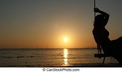 Beautiful young woman swinging on a swing at golden sunset through the sun on tropical beach. slow motion.