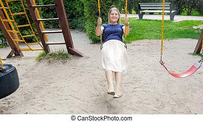 Beautiful young woman swinging on children playground