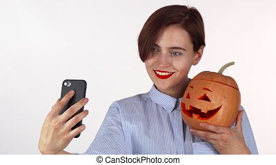 Beautiful young woman taking selfies with Halloween pumpkin
