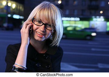Beautiful young woman talking on mobile phone in night city