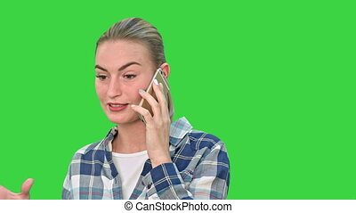 Beautiful young woman talking on mobile phone seriously on a Green Screen, Chroma Key.
