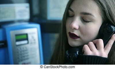 Beautiful young woman talking on payphone