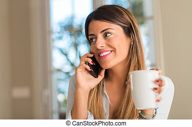 Beautiful young woman talking on phone while drinking cup of coffee at home.