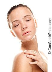 Beautiful young woman touching her skin.