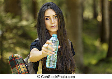 Beautiful young woman tourist in the park. Drink water.