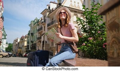 Beautiful Young Woman tourist Pleasant with city map and suitcase in the City Center.