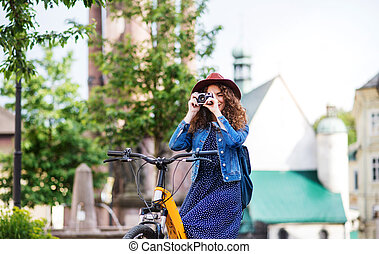 Beautiful young woman tourist with electric scooter in small town, using camera.