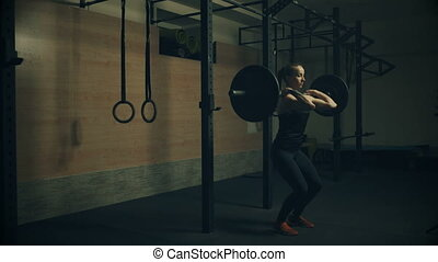 Beautiful young woman training with dumbbells in gym -...