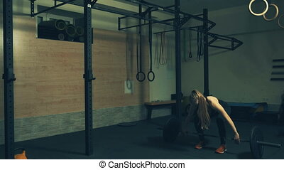 Beautiful young woman training with dumbbells in gym